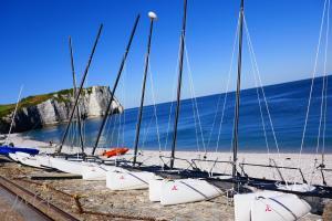 France, Etretat, the sea, catamarans and the picturesque chalk cliffs.