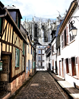 Beauvais, France. A view onto the huge Gothic cathedral seen from a street with well preserved old buildings. Buildings constructed of half-timbered walls are typical for this part of Europe.