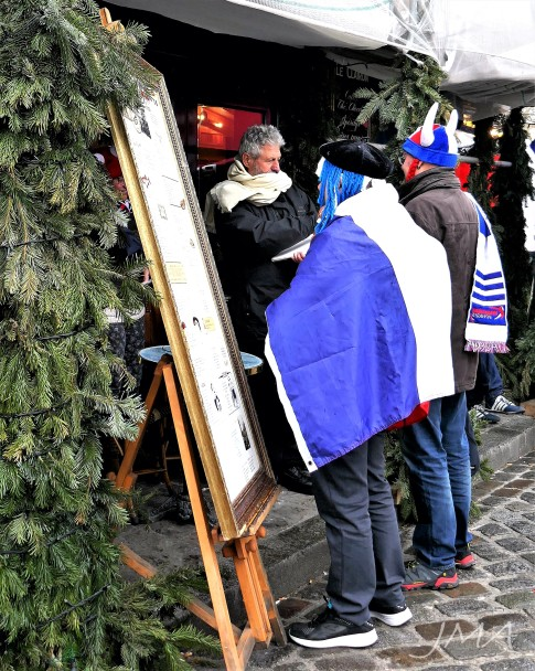 An illustration artist taking a picture of two French rugby fans at the main square of Mont Martre