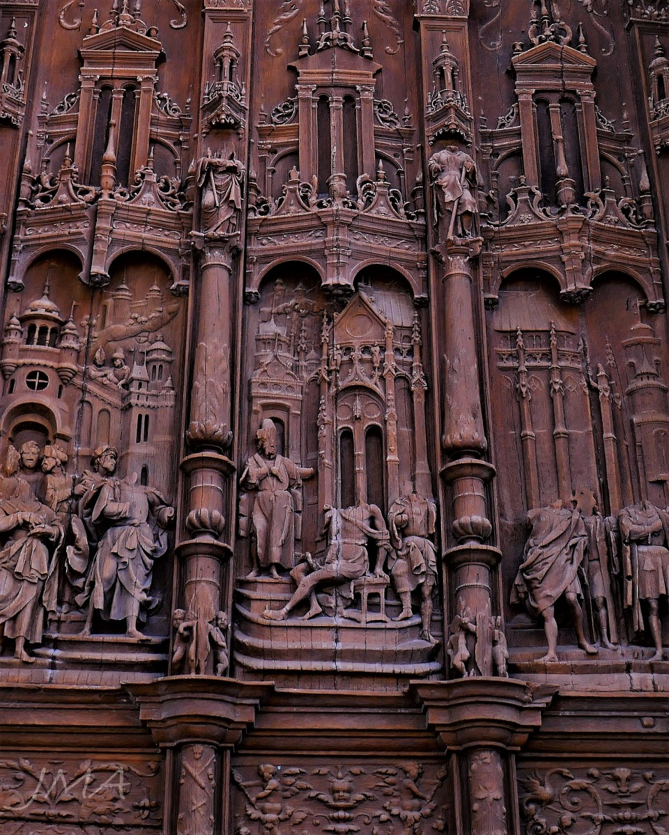 Traveling France. Beheaded figures of saints on a wooden relief. The door to the cathedral of Beauvais, France.