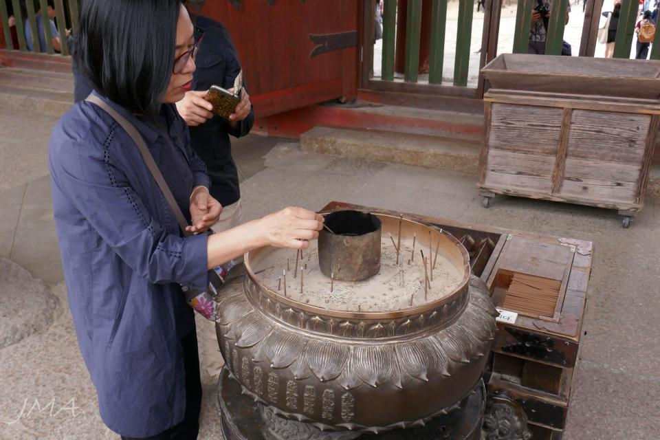 A woman performing a cleansing ceremony in a Buddhist temple in Japan.