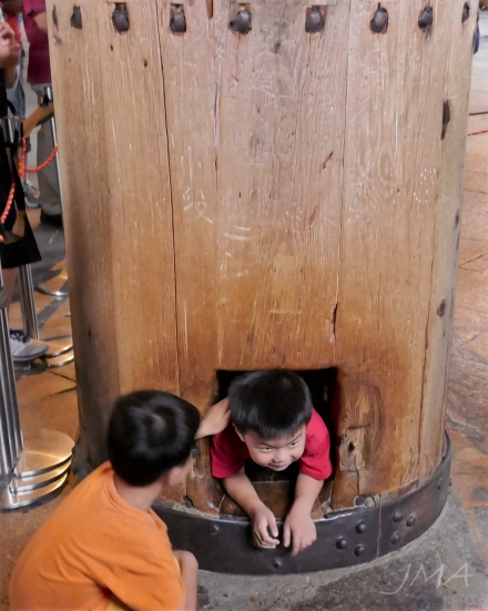 Children passing a hole in a pillar supporting the Great Buddha Hall in the Tōdai-ji temple complex in Nara, Japan.